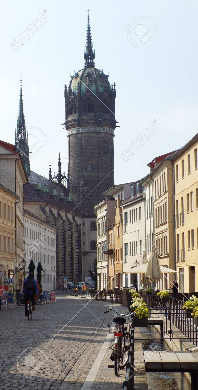 Castle Street in the old town of Wittenberg; in the background the tower of the Castle Church of All Saints, Wittenberg, Germany 04.12.2016 - At the door of the Castle Church in Wittenberg reformer Martin Luther nailed his 95 theses. By Luther and Melanch - 69414729