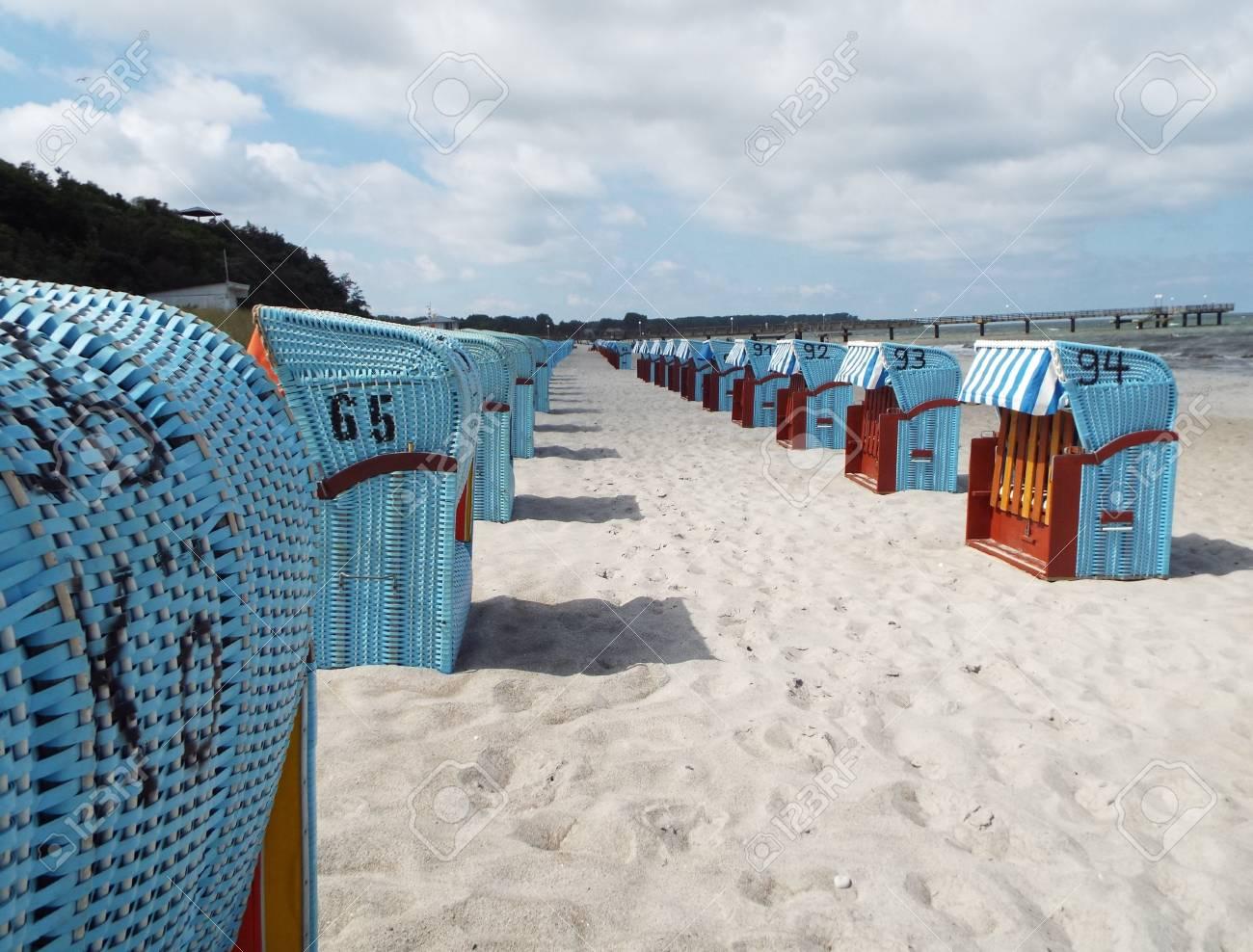 Preseason at the Baltic Sea - Blue beach baskets on the beach under a slightly cloudy sky. - 76660121
