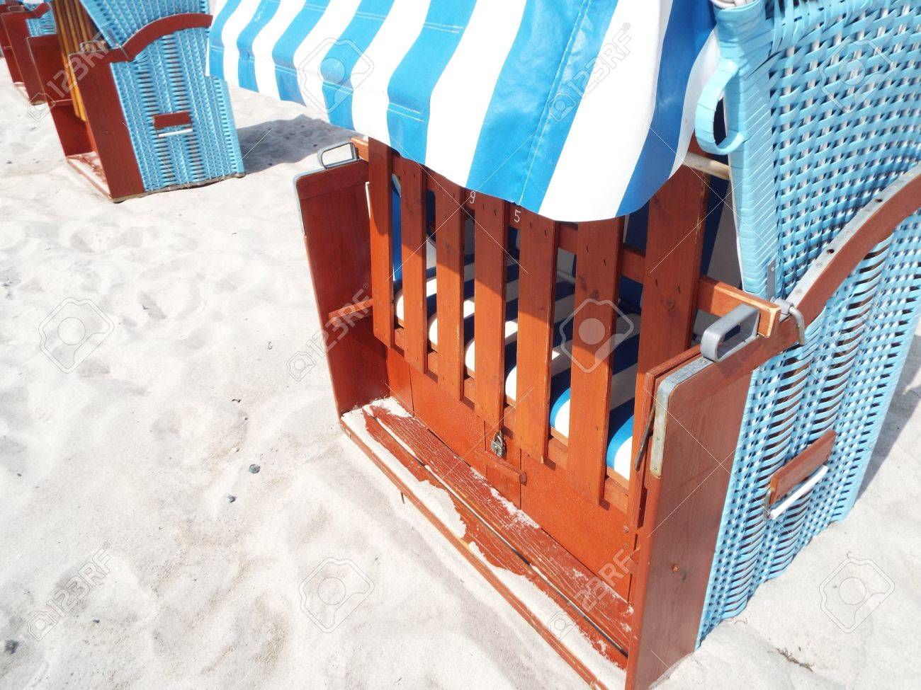 Preseason at the Baltic Sea - Partial view of a blue beach basket on a sandy beach. - 77355980