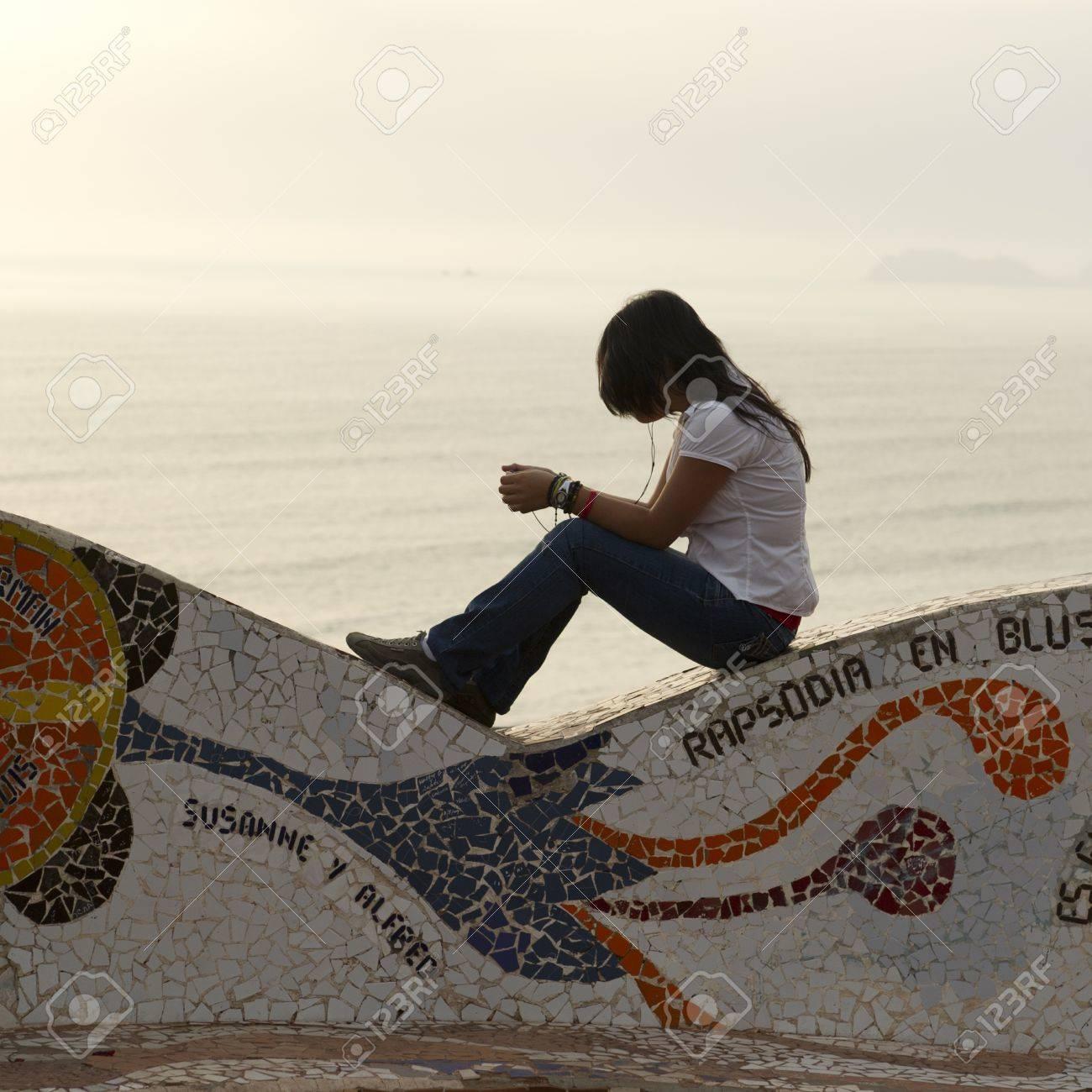 Woman listening to MP3 player in a park, El Parque Del Amor, Av De La Aviacion, Miraflores District, Lima Province, Peru Stock Photo - 16783717