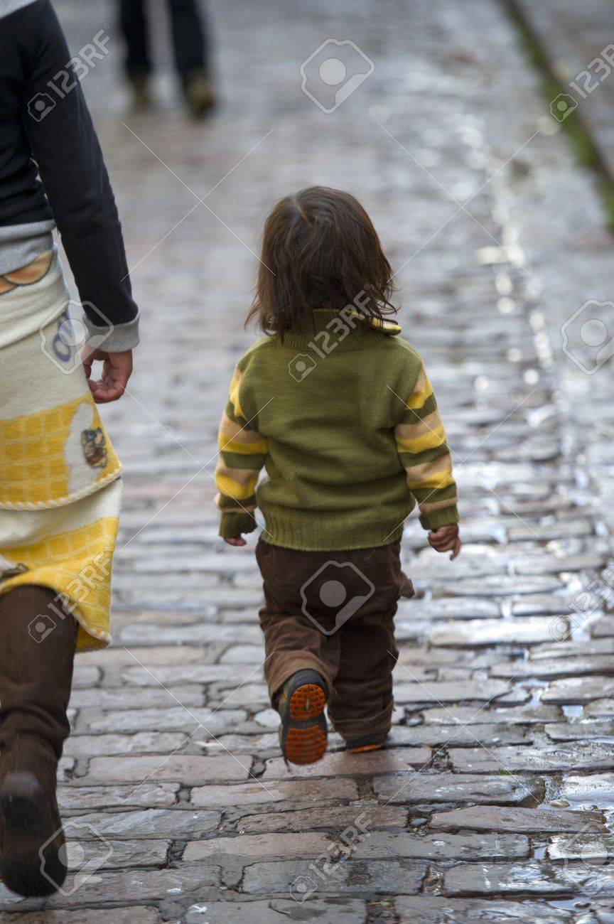Child walking with mother on a cobblestone walkway, Cuzco, Peru Stock Photo - 16807992