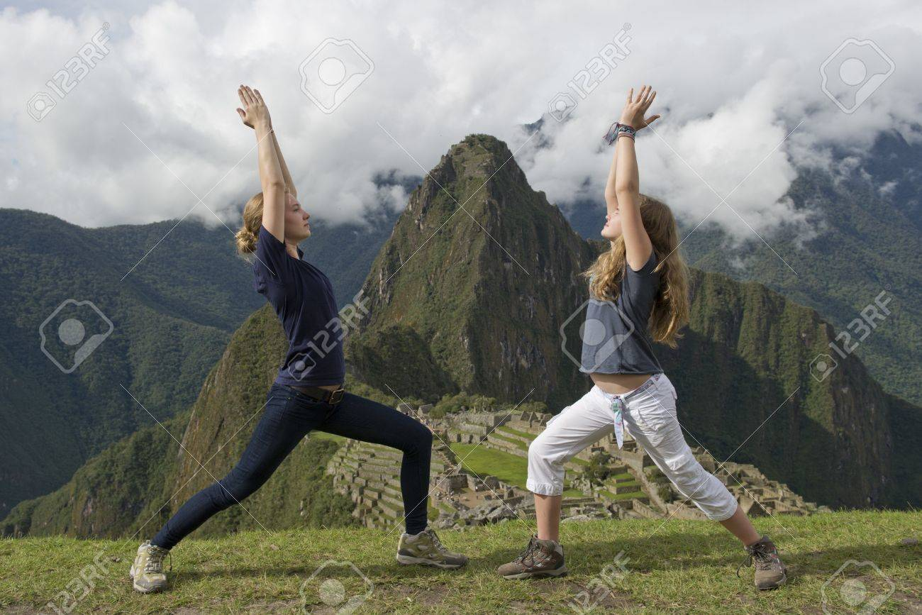 Teenage girls doing warrior 1 pose with The Lost City of The Incas in the background, Machu Picchu, Cusco Region, Peru Stock Photo - 17227754