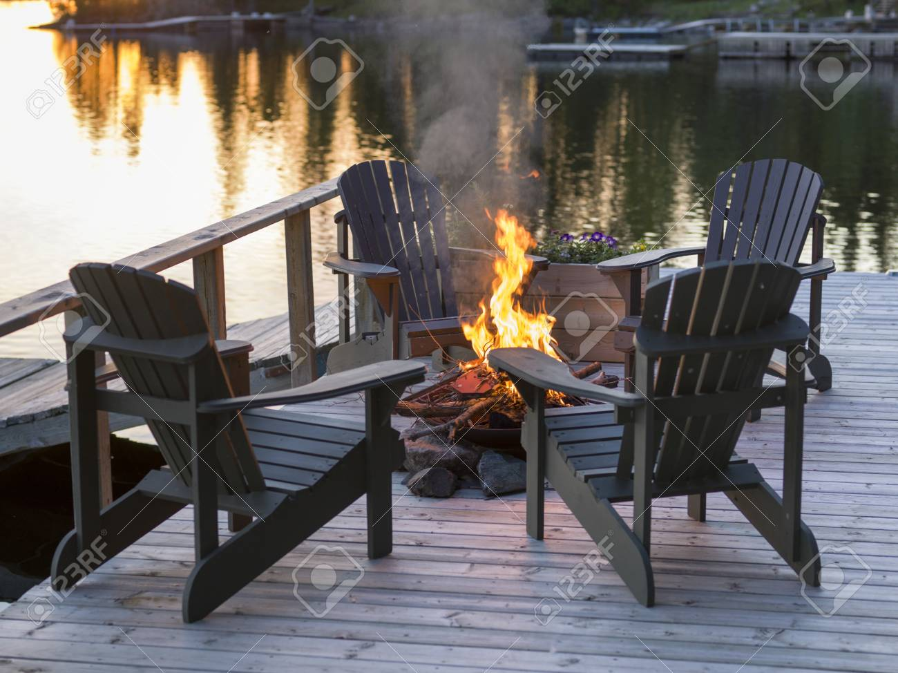 Adirondack Chairs And Campfire On A Dock Lake Of The Woods