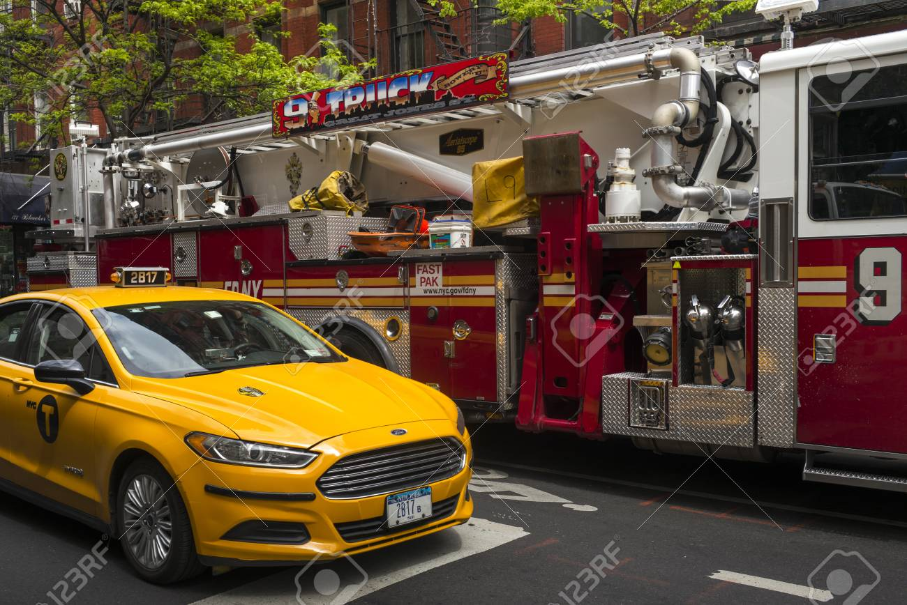 Yellow taxi and fire engine on street, New York City, New York