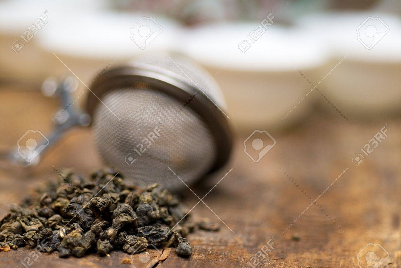 dry green chinese tea set,with strainer closeup,cups and teapot on background over old wood board Stock Photo - 6971744