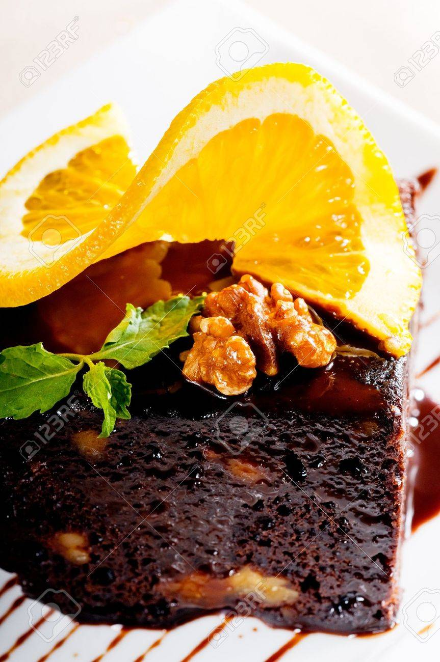 fresh baked delicious chocolate and walnuts cake with slice of orance on top and mint leaf Stock Photo - 9109555