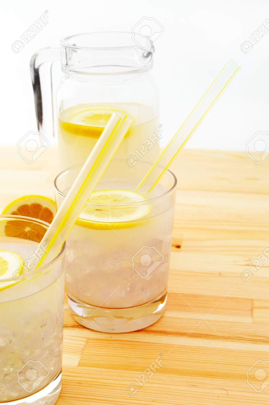 fresh lemonade drink with lemon slice closeup and pitcher carafe over pinewood table Stock Photo - 15496529