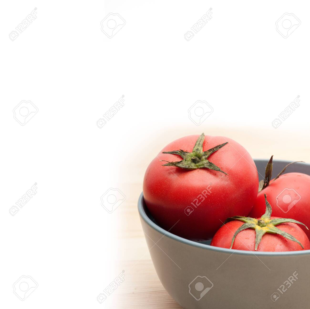 fresh ripe tomatoes on a blue bowl over pine wood table Stock Photo - 15226435