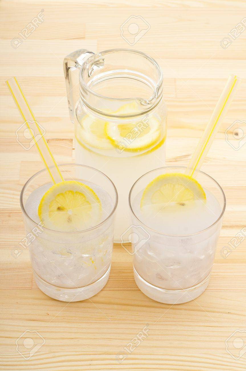 fresh lemonade drink with lemon slice closeup and pitcher carafe over pinewood table Stock Photo - 15279517