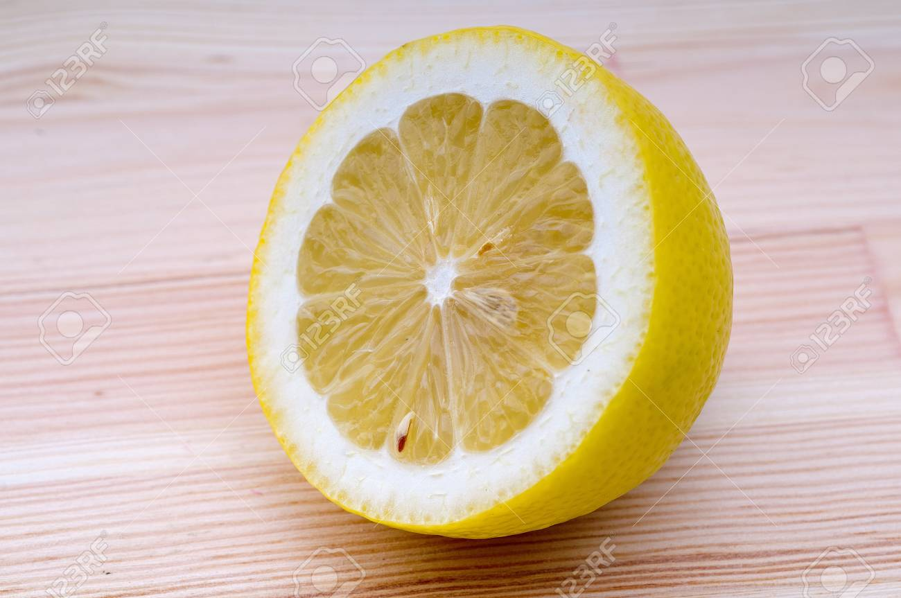 fresh ripe lemon cutted in half closedup over wood table Stock Photo - 15279522