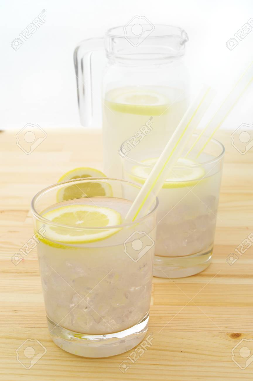 fresh lemonade drink with lemon slice closeup and pitcher carafe over pinewood table Stock Photo - 16216820