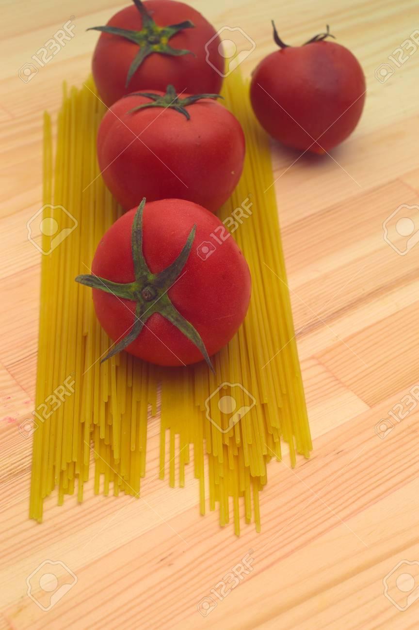 fresh tomato and raw spaghetti pasta over pine wood table Stock Photo - 16216847