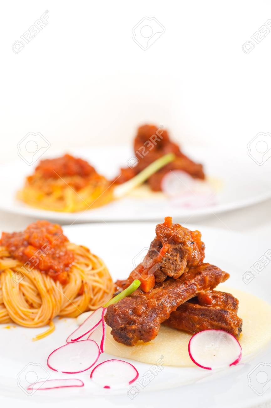 traditional Italian spaghetti pasta with pork ribbs sauce served on polenta bed Stock Photo - 19016794