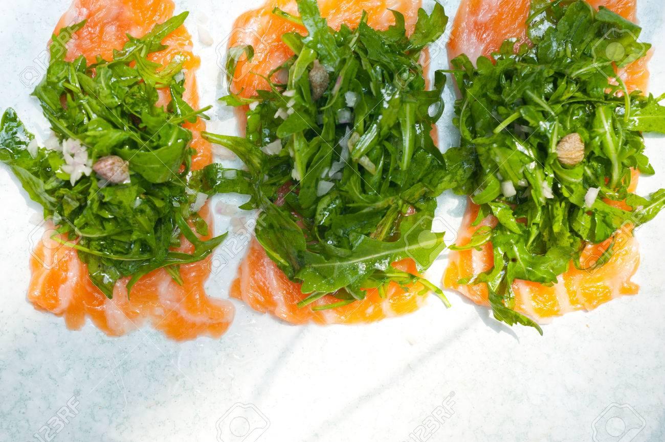 Fresh Salmon Carpaccio Sushi Sashimi With Arugula Rocket Salad And Caper On Top Stock Photo