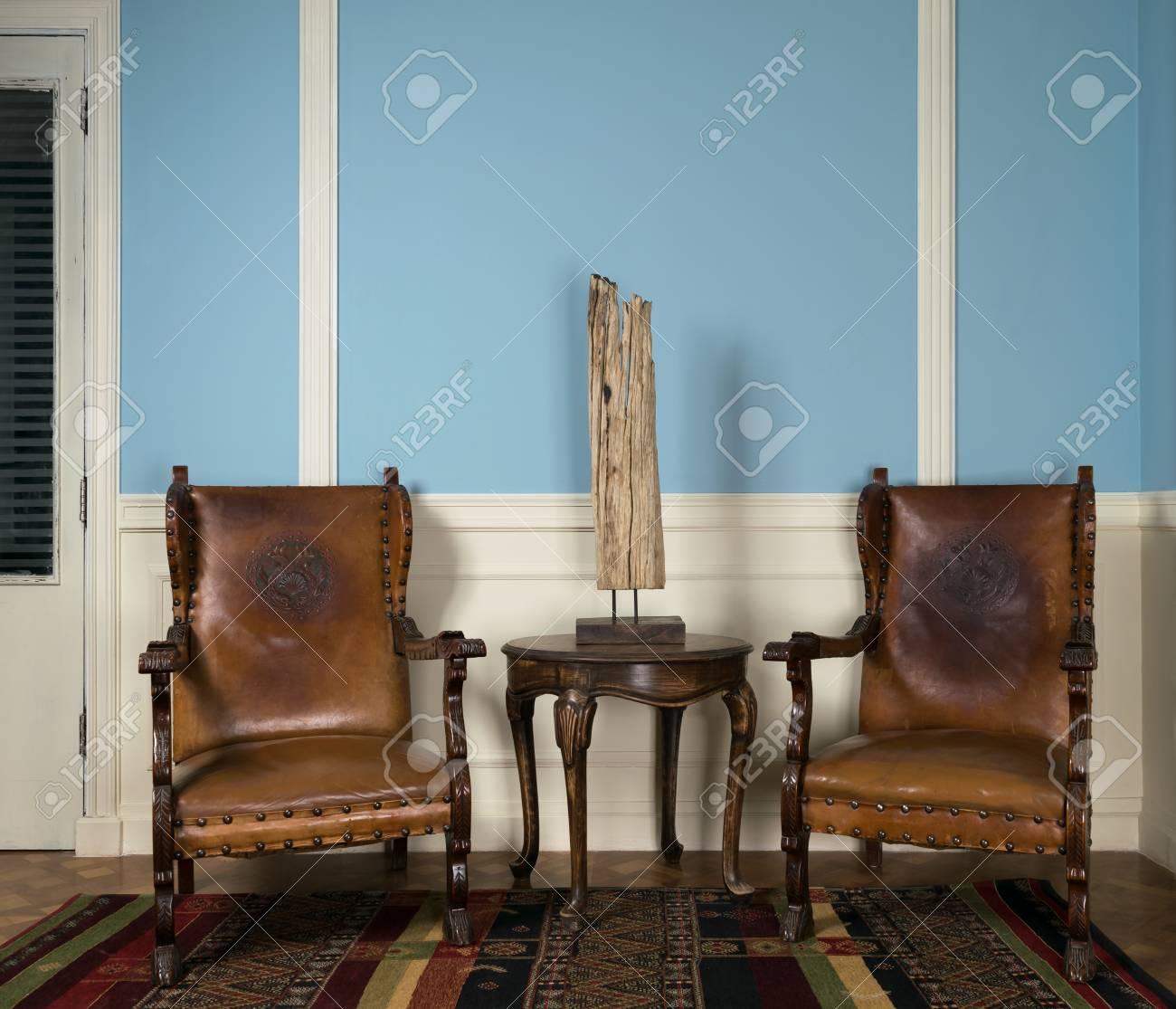 Composition De Deux Fauteuils Retro En Bois Et Lampe De Table Sur Une Petite Table Basse Ronde Sur Un Tapis Colore Orne