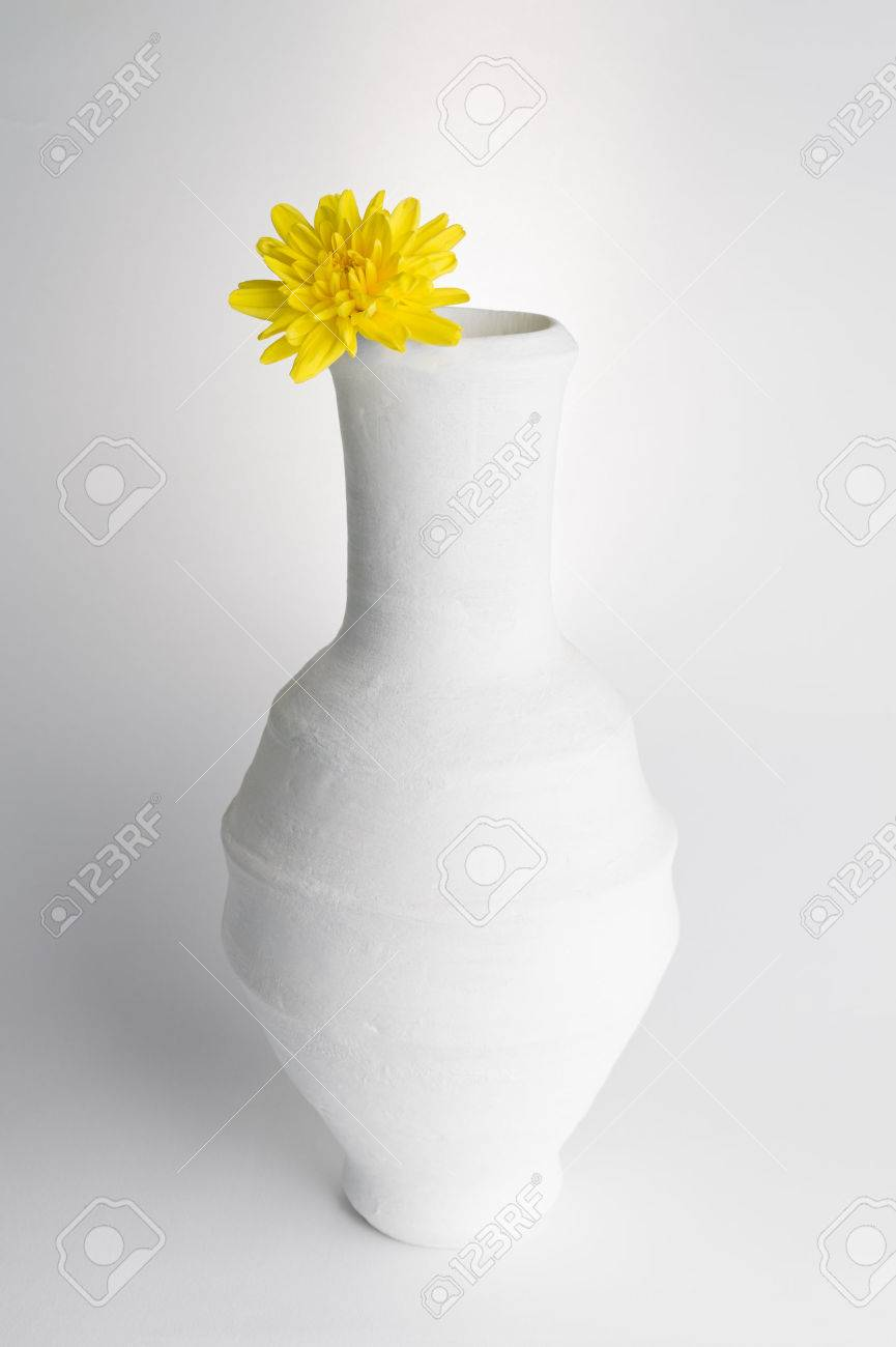 Still life composition of white pottery vase and yellow flower still life composition of white pottery vase and yellow flower on white background stock photo reviewsmspy