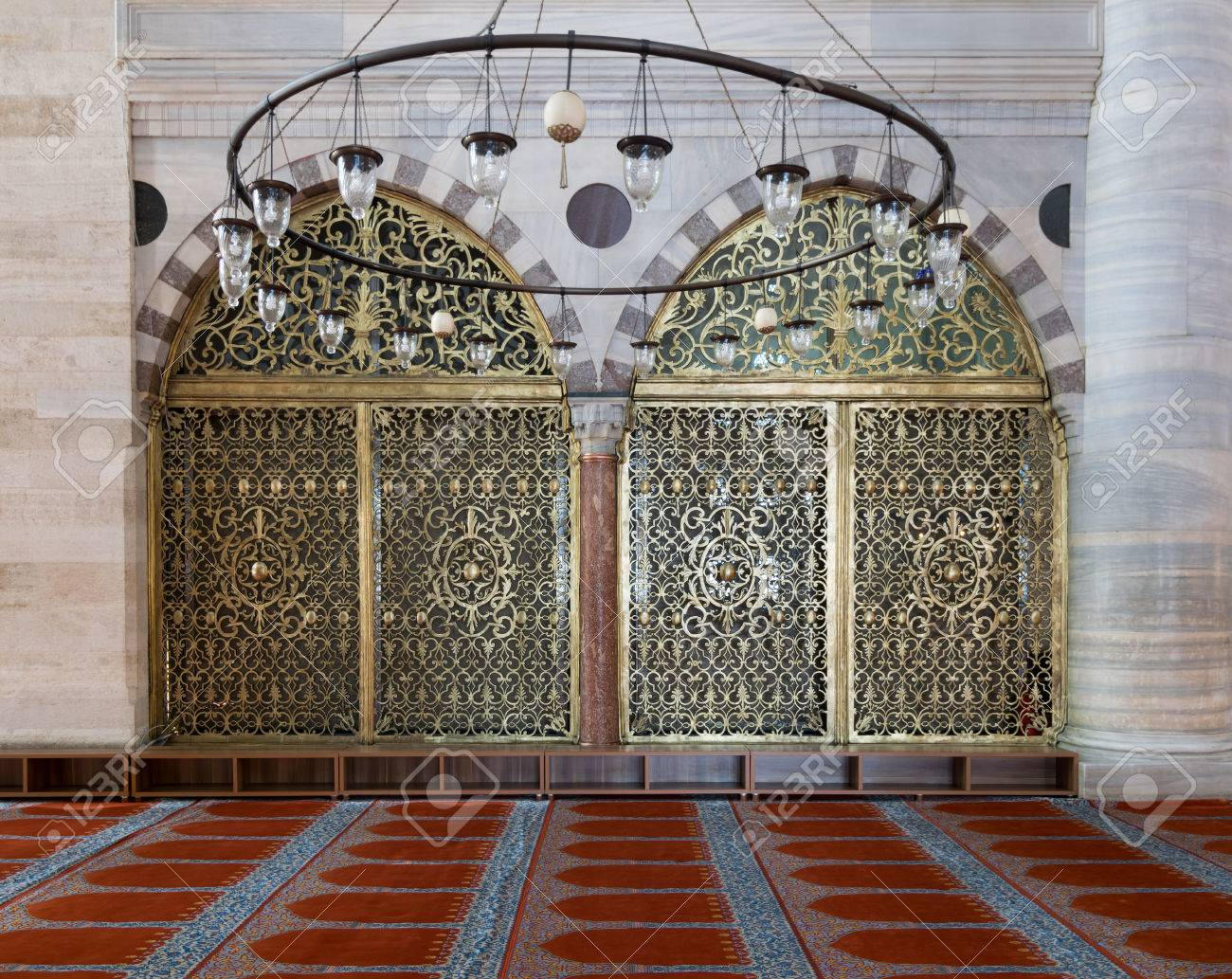 Interior Shot Of Two Arched Ornate Engraved Golden Doors, Big Chandelier  Over Marble Wall With