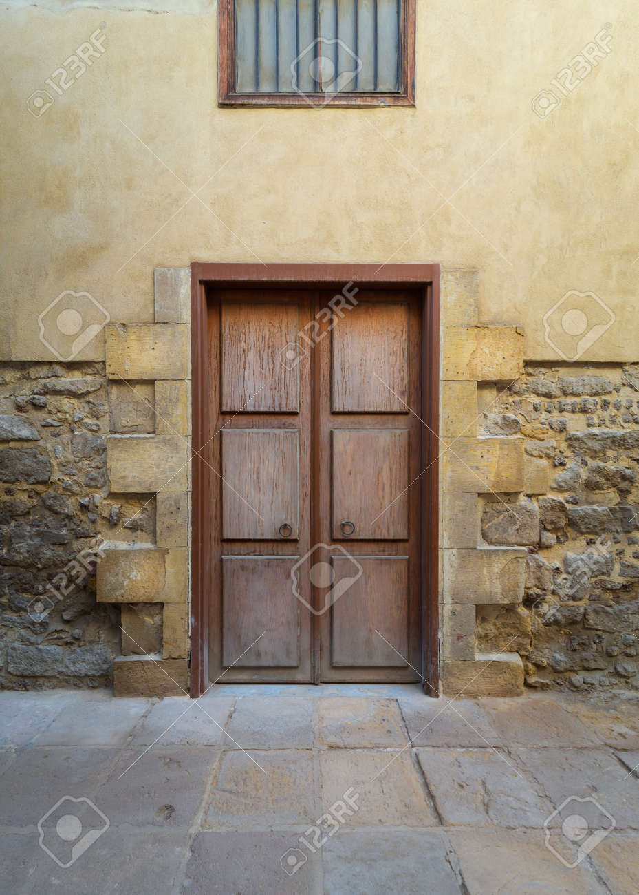 Facade of old abandoned stone bricks wall with decorated wooden door and wrought iron window above - 151605777