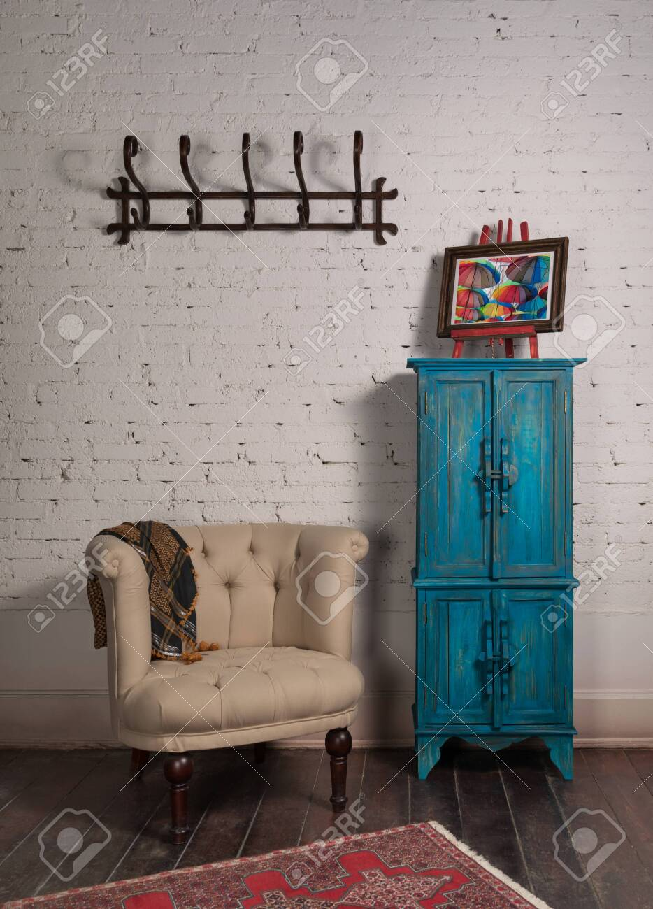Classic beige armchair with wooden legs, vintage turquoise cupboard, wall hanger, and ornate scarf on white bricks wall and grunge wooden parquet with red decorated carpet - 151698897