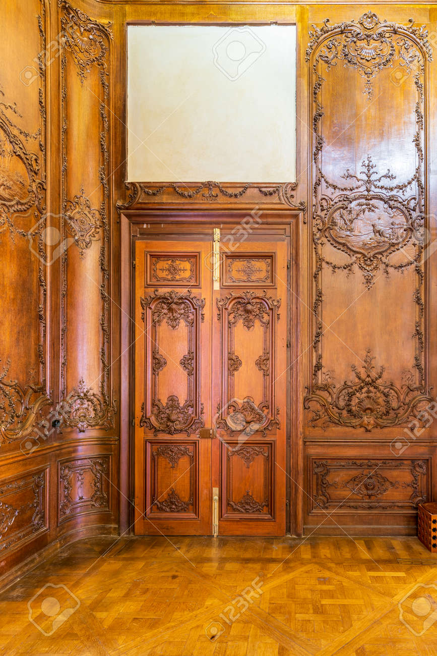 Front view of closed elegant lumber door with engraved decorations, installed in wooden ornamental archway leading to old building - 159853886