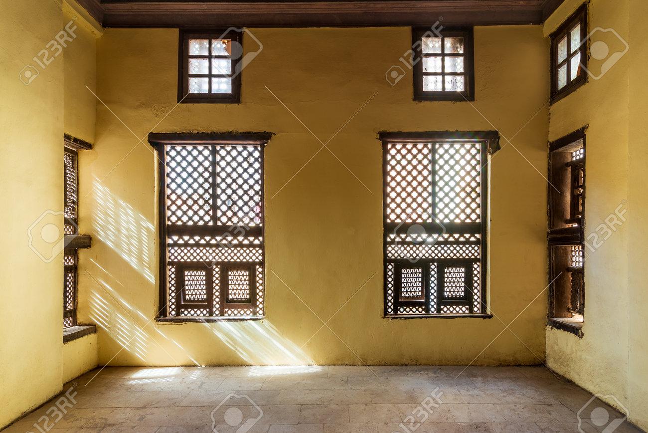 Facade of two Interleaved grunge wooden ornate windows - Mashrabiya - in stone wall in abandoned building - 161211675