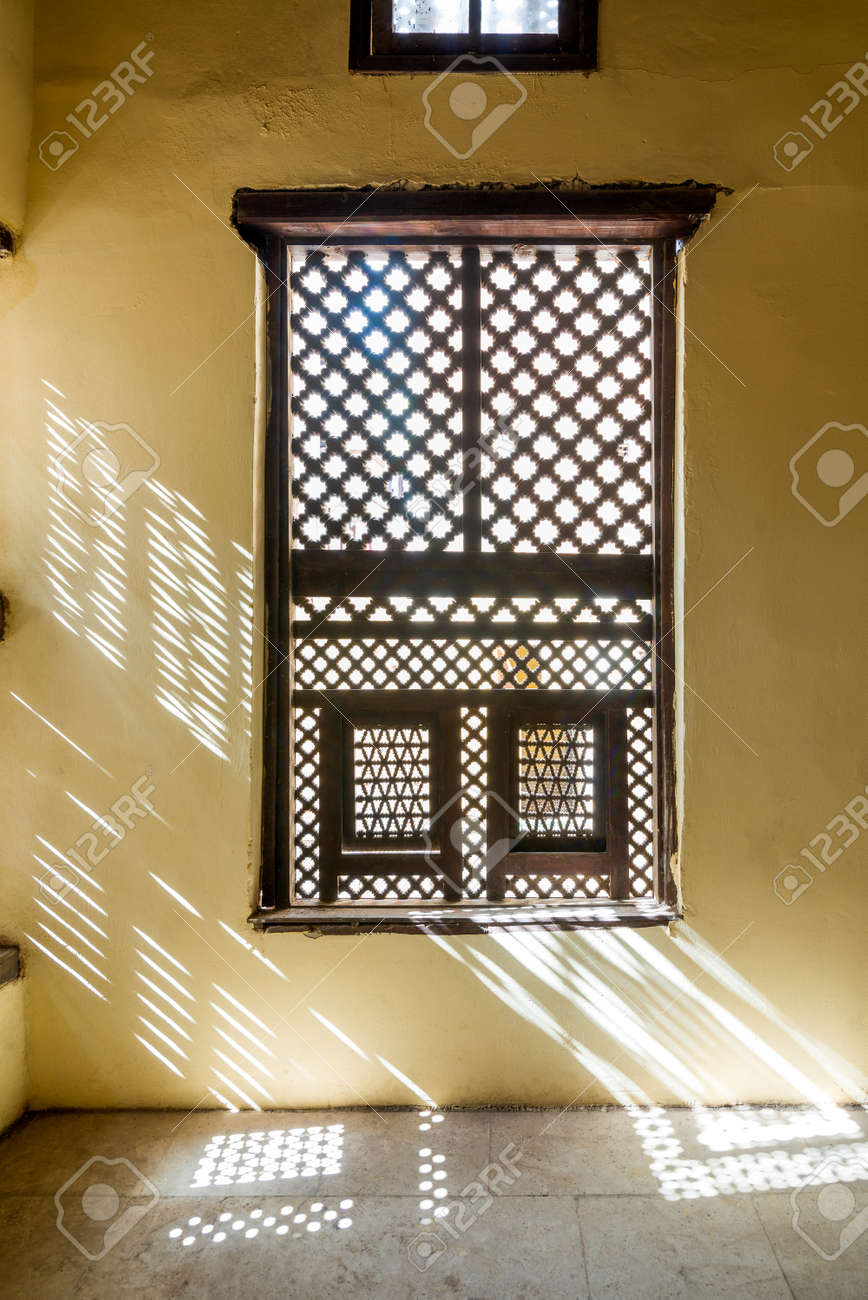 Single interleaved grunge wooden ornate windows - Mashrabiya - in stone wall at abandoned building - 162122684