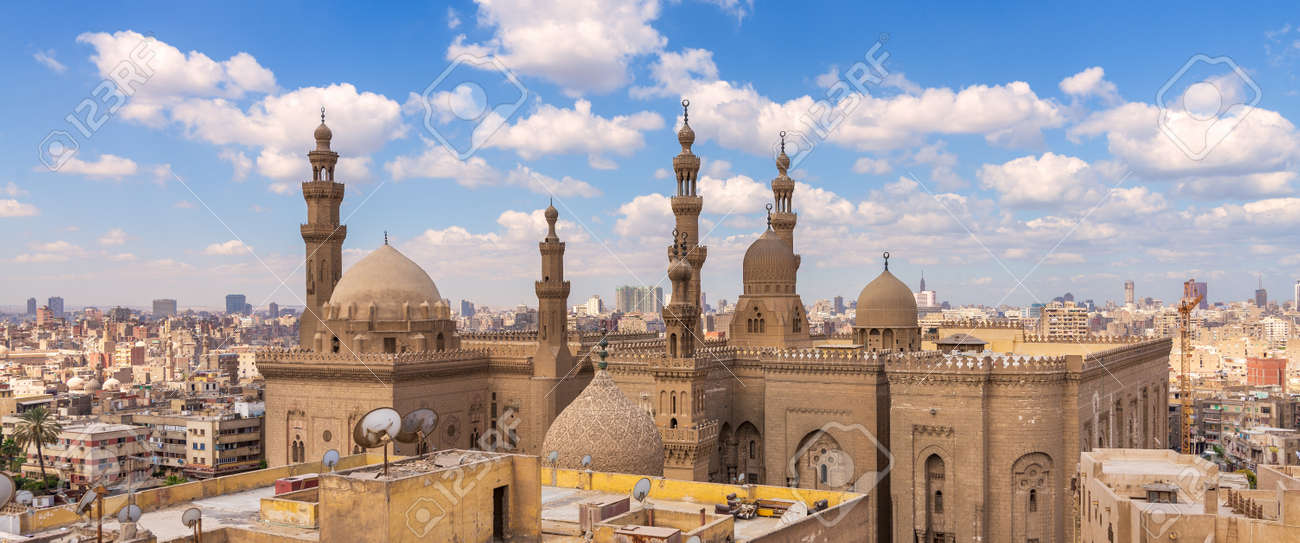 Aerial day shot of minarets and domes of Sultan Hasan mosque and Al Rifai Mosque mediating shabby buildings with satellite dishes in cloudy day, Old Cairo, Egypt - 170694208