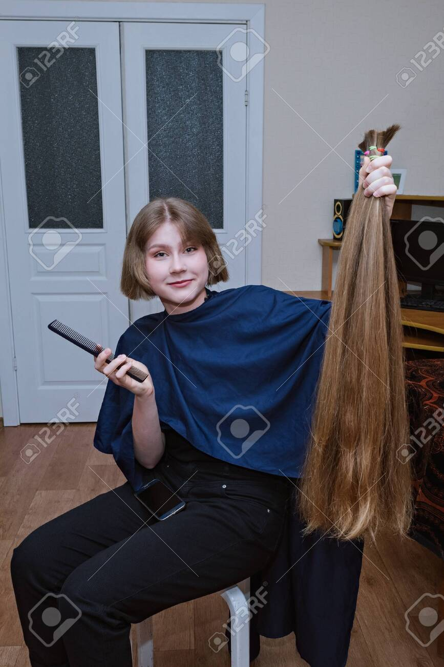 Young blonde girl cut very long hair at home - 148352041