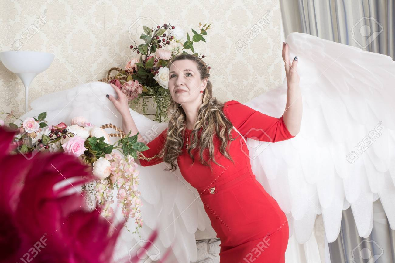 330182408 Stock Photo - Ugly woman in a red dress with white angel wings posing in  the Studio