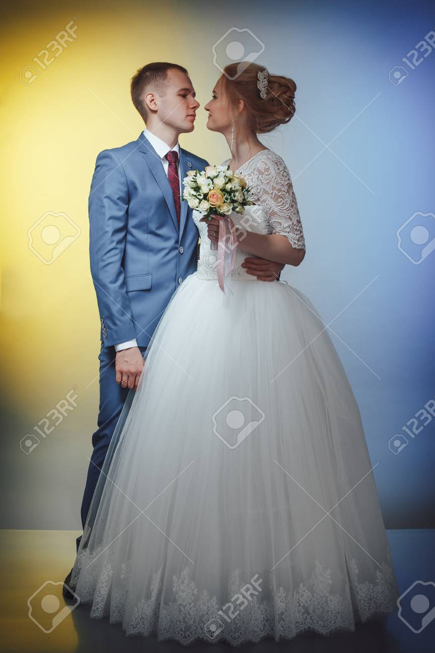 Beautiful Bride In A White Dress And A Young Groom In A Blue.. Stock ...