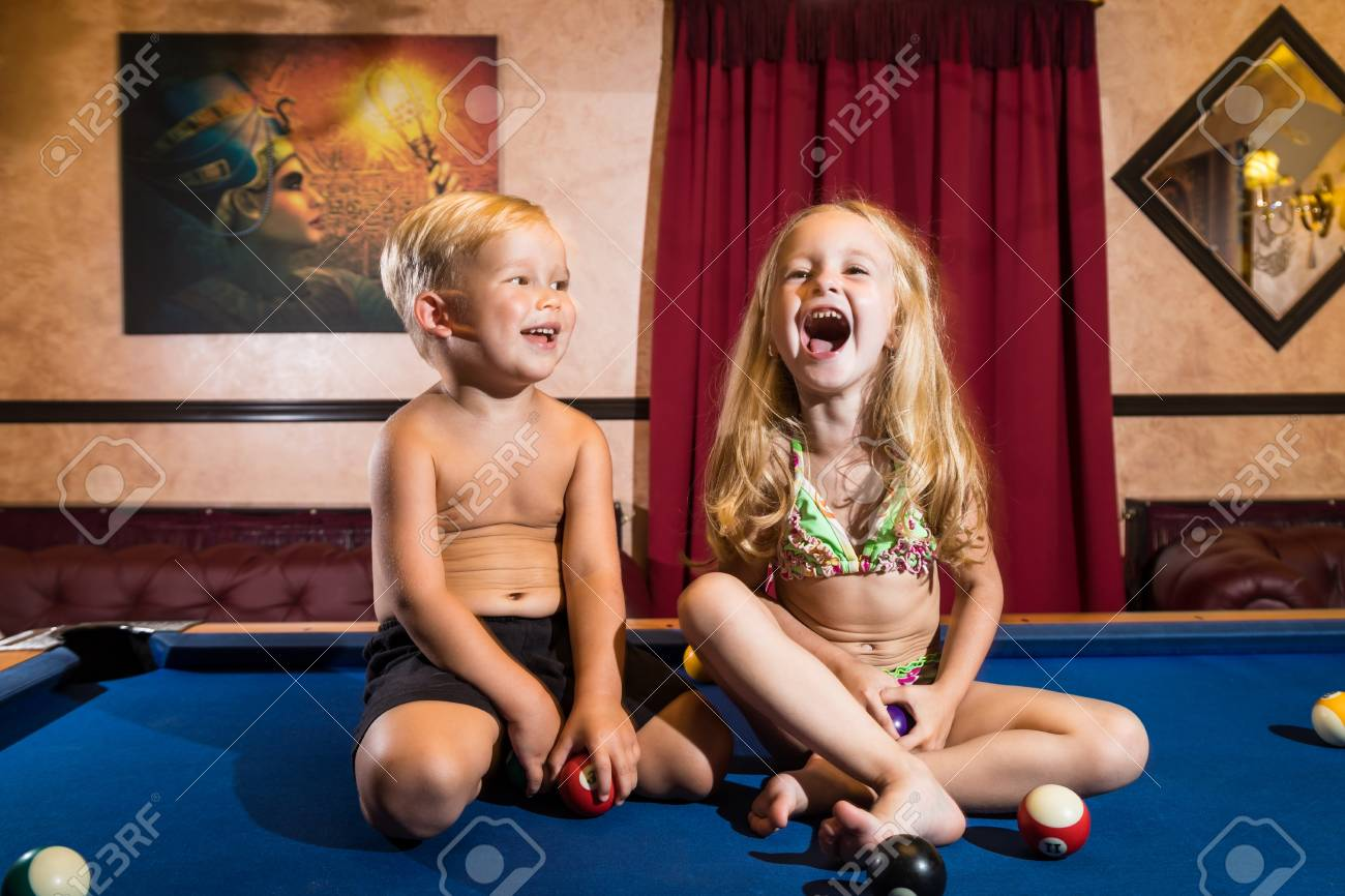 Kirov, Russia - July 18, 2018: Cute children sitting on the billiards table and balls arround. Barefoot kids. Boy and girl, brother and sister, friens have fun together during photosoot - 115186616