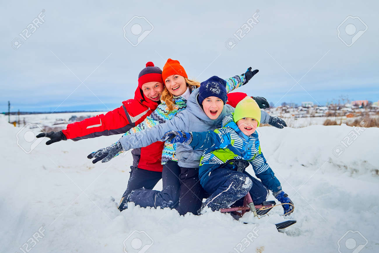 Portrait of a family with four people having fun in the snow - 121691457