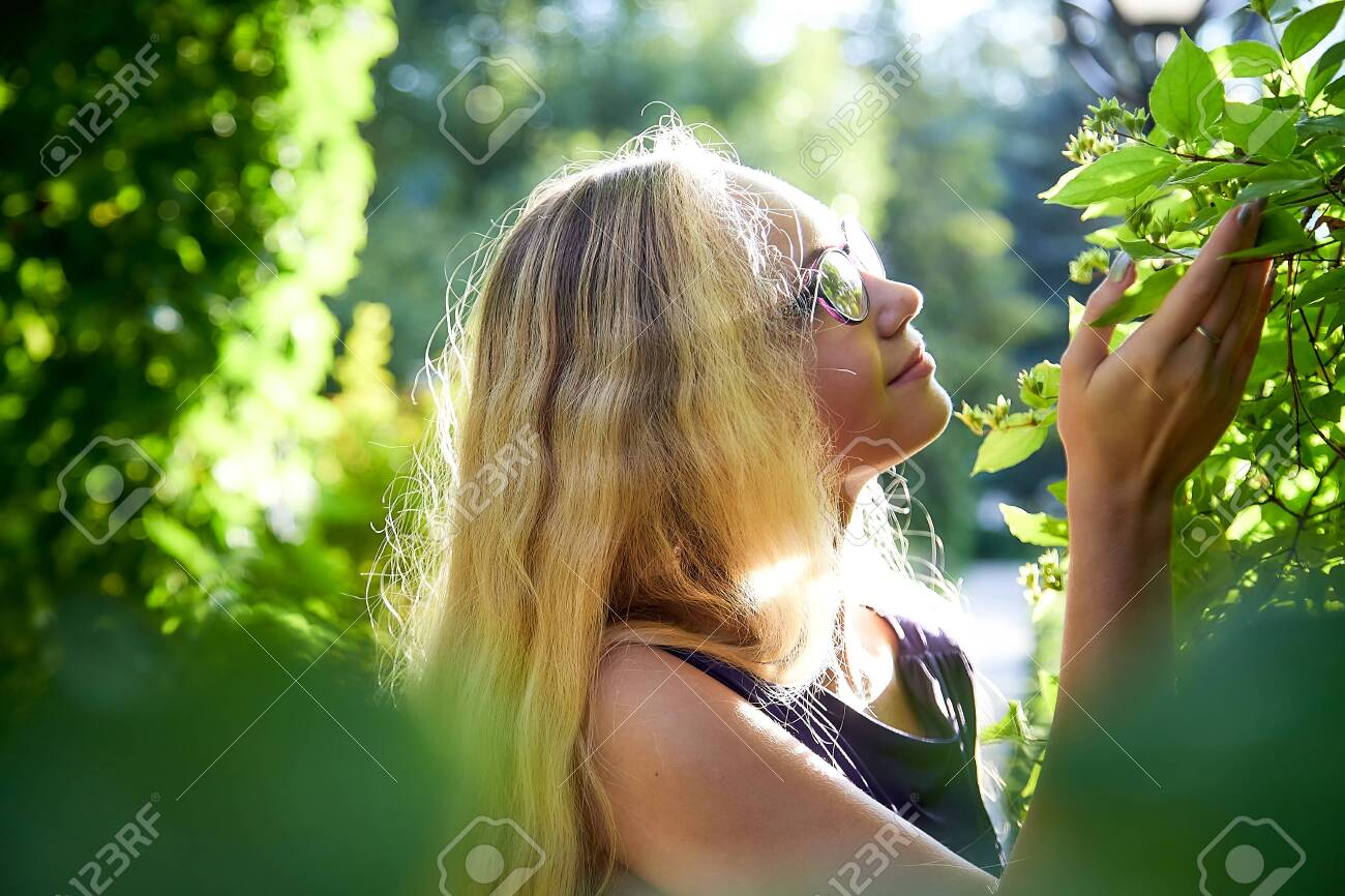 Pretty teenage girl 14-16 year old with curly long blonde hair in beautiful adult dress in the green park in a summer day outdoors. Beautiful outdoors portrait - 136668124
