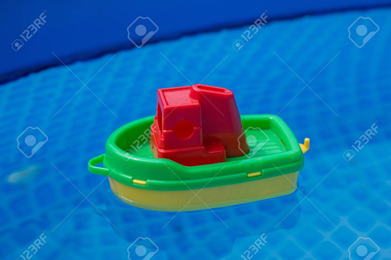 Small Plastic Toy Boat Floating In A Swimming Pool Stock Photo