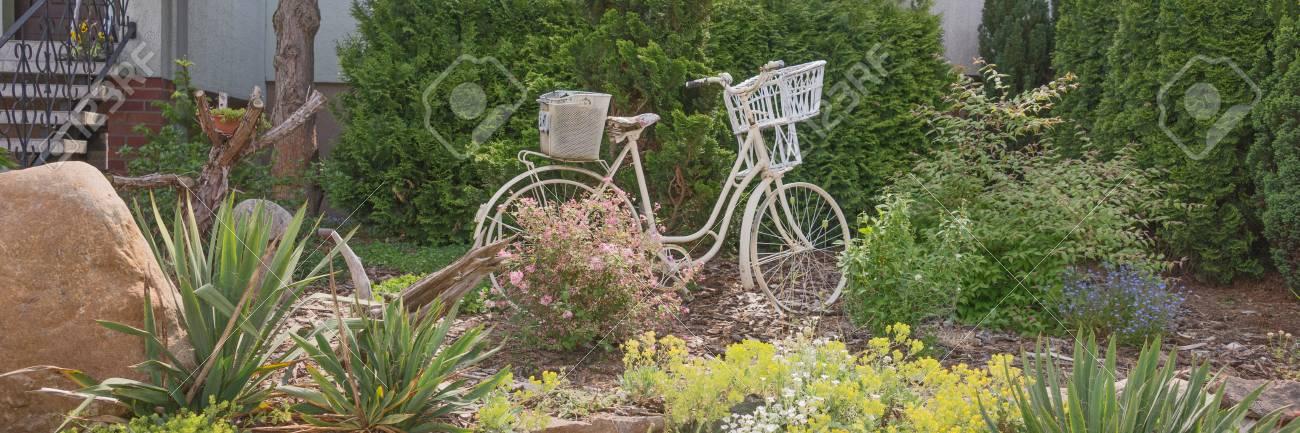Vieux vélo blanc dans le jardin comme décoration