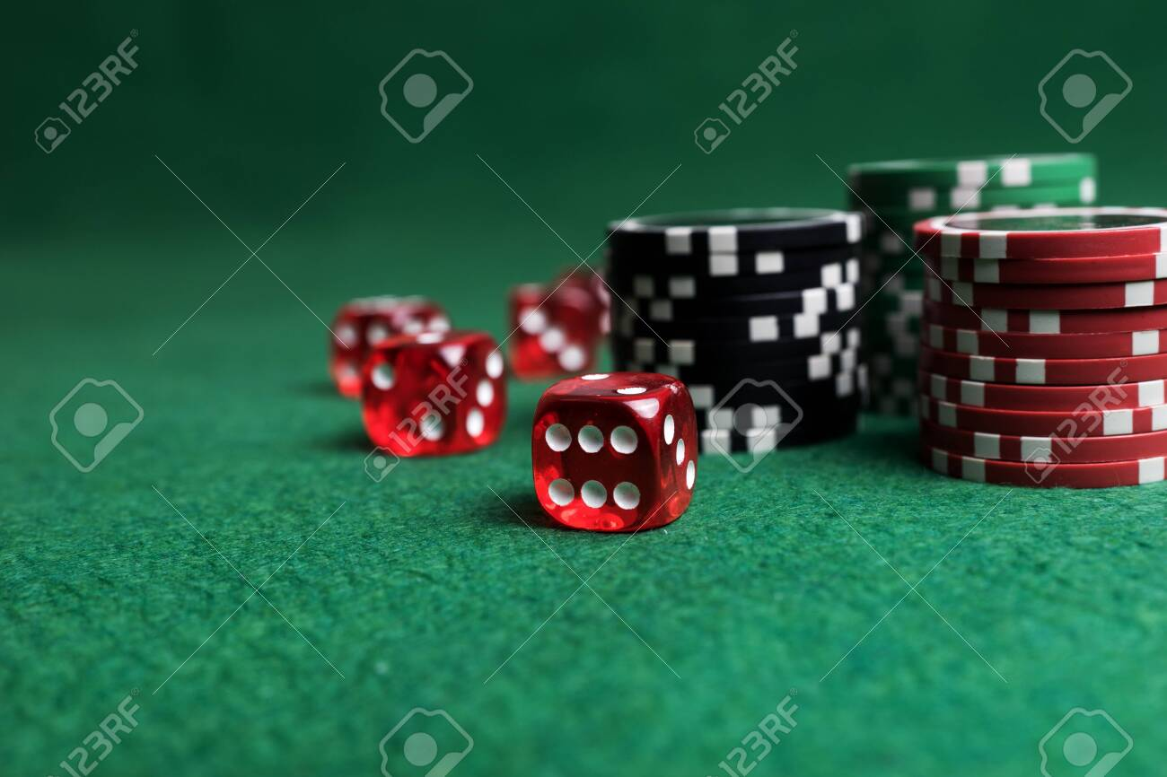 Casino game. Poker chips and red dice on green table - 123354002