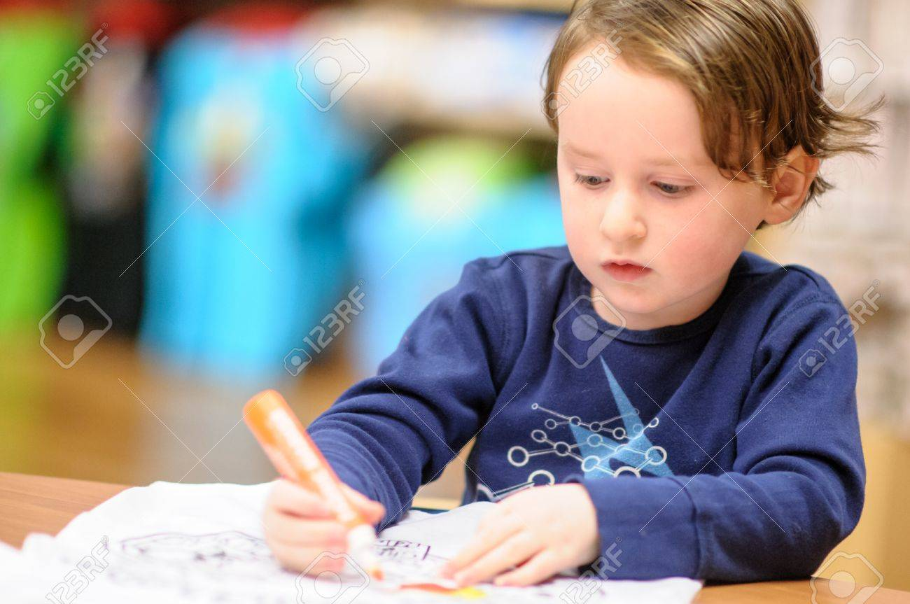 Young boy sitting down at desk indoors coloring with markers