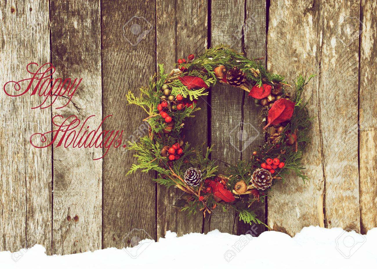 Christmas card design featuring a home made christmas wreath with natural decorations hanging on a rustic wooden wall with text  Happy Holidays Stock Photo - 15273307