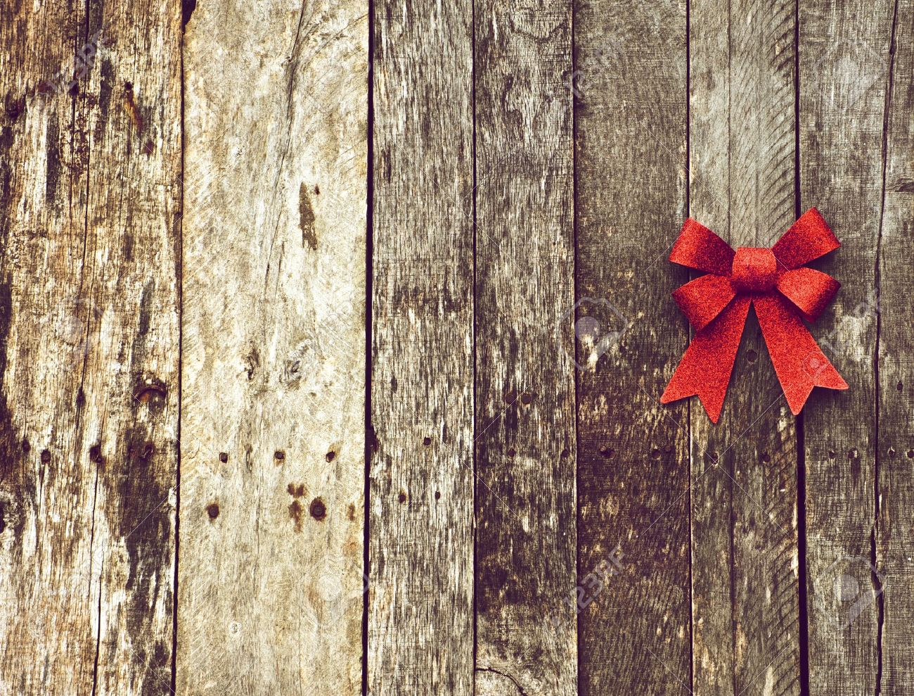 Richly Toned High Contrast Christmas Background With A Sparkling Red Bow On Grunge