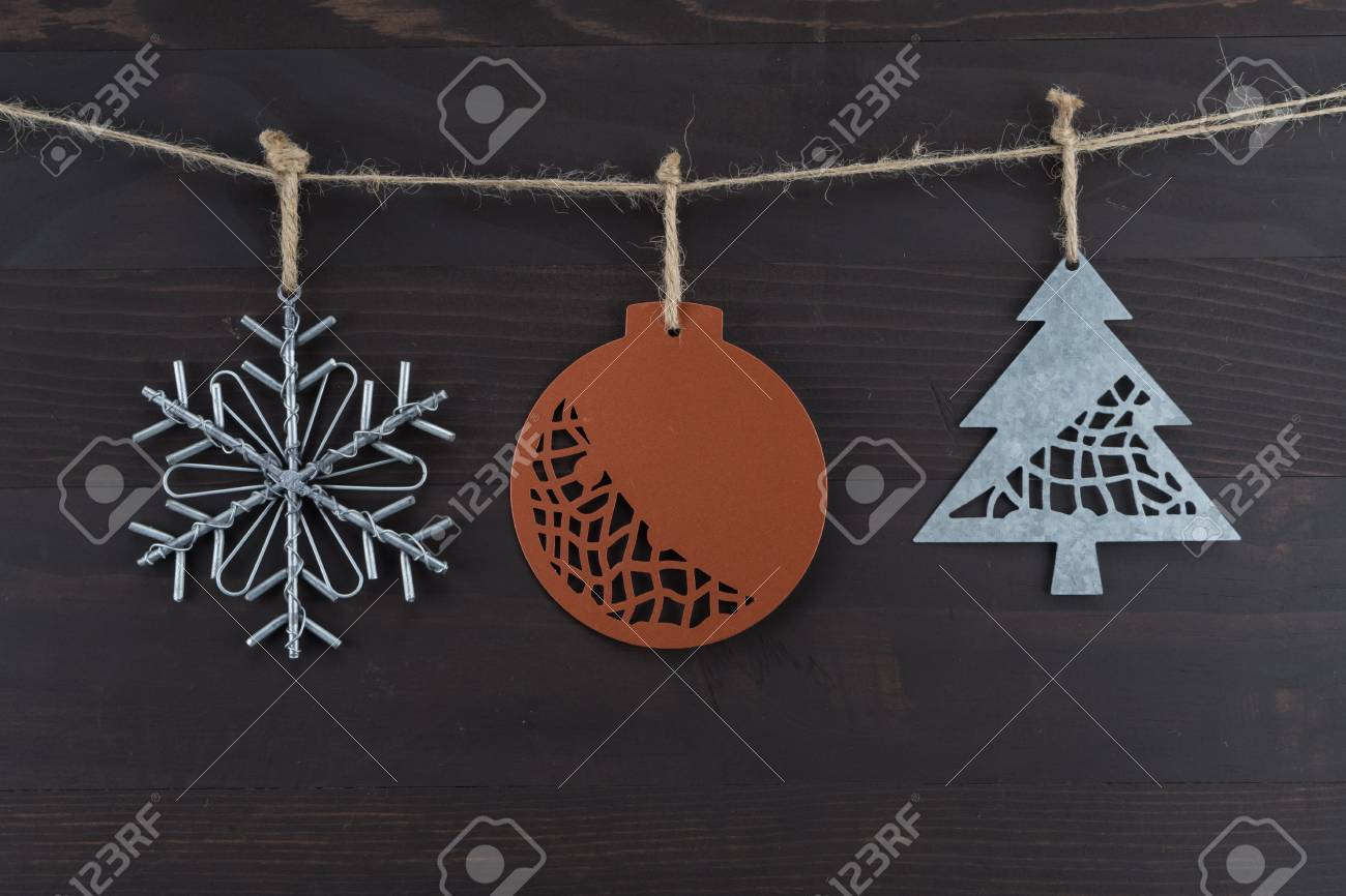 Three Rustic Metal Christmas Ornaments Hanging From Twine