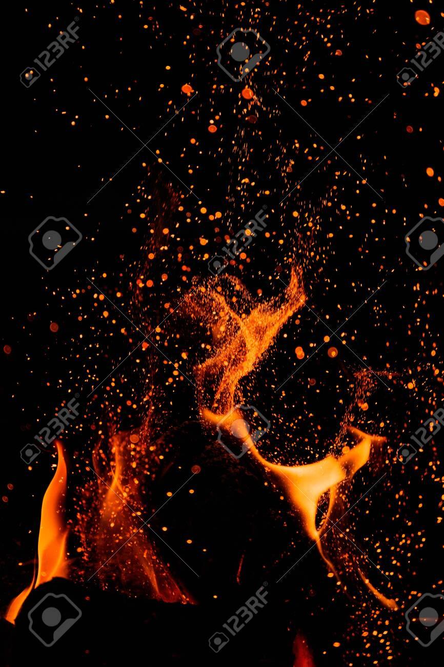Flames Lick As Embers Rise against dark sky - 135061969