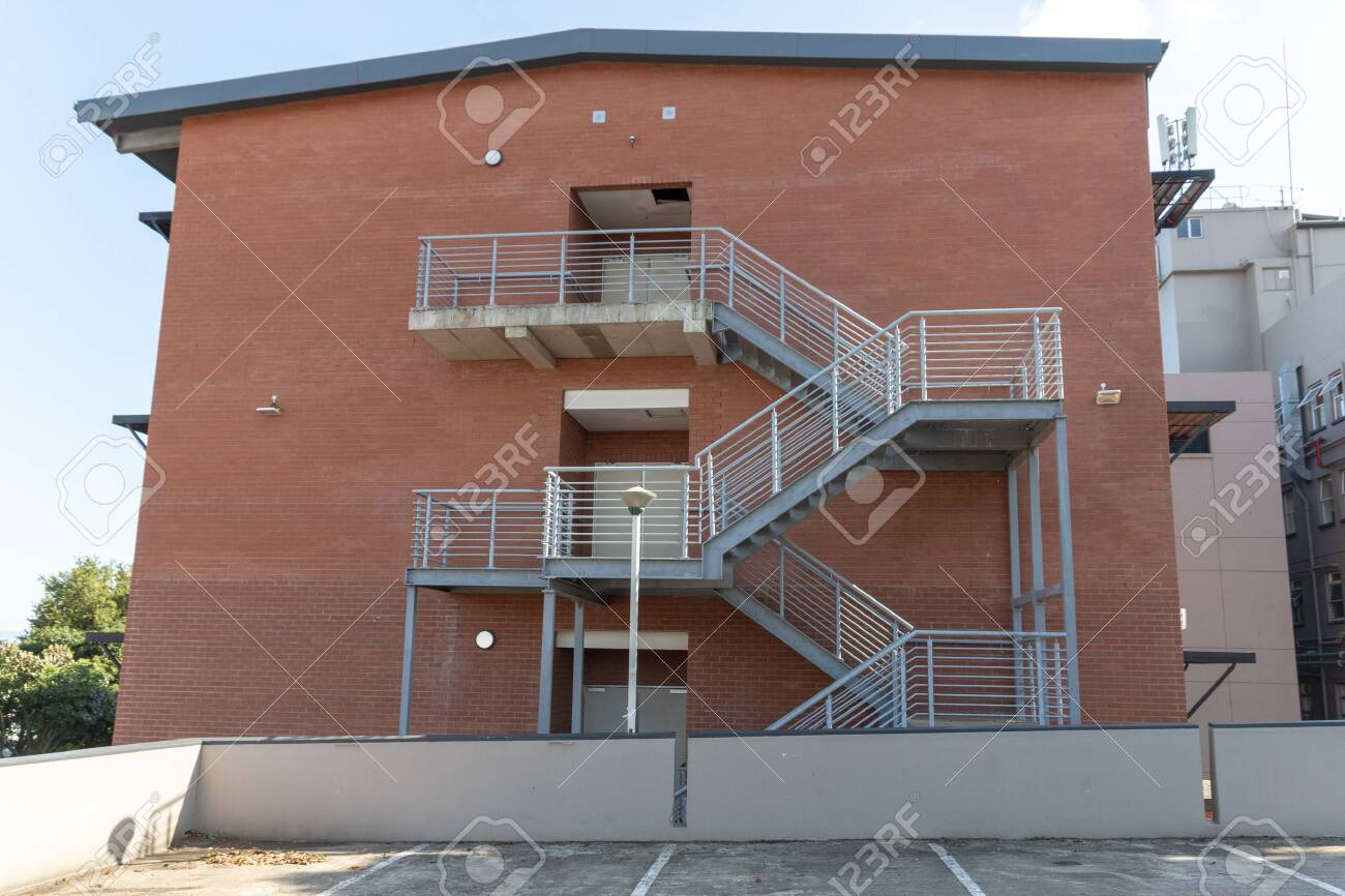 A close up view of a metal stair case going up the side of a newly built building - 139016820