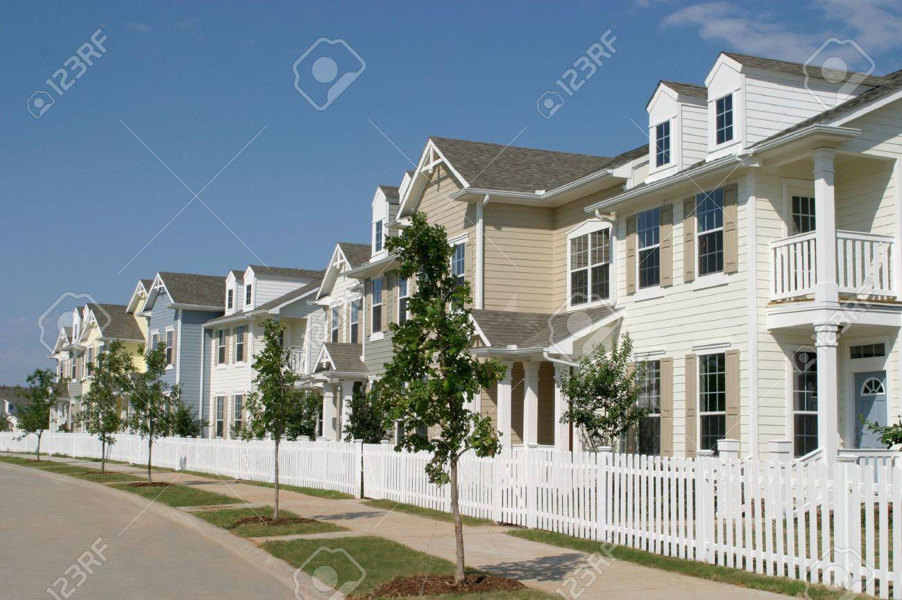 Long row of suburban townhouses with a white picket fence in front. Stock Photo - 466684