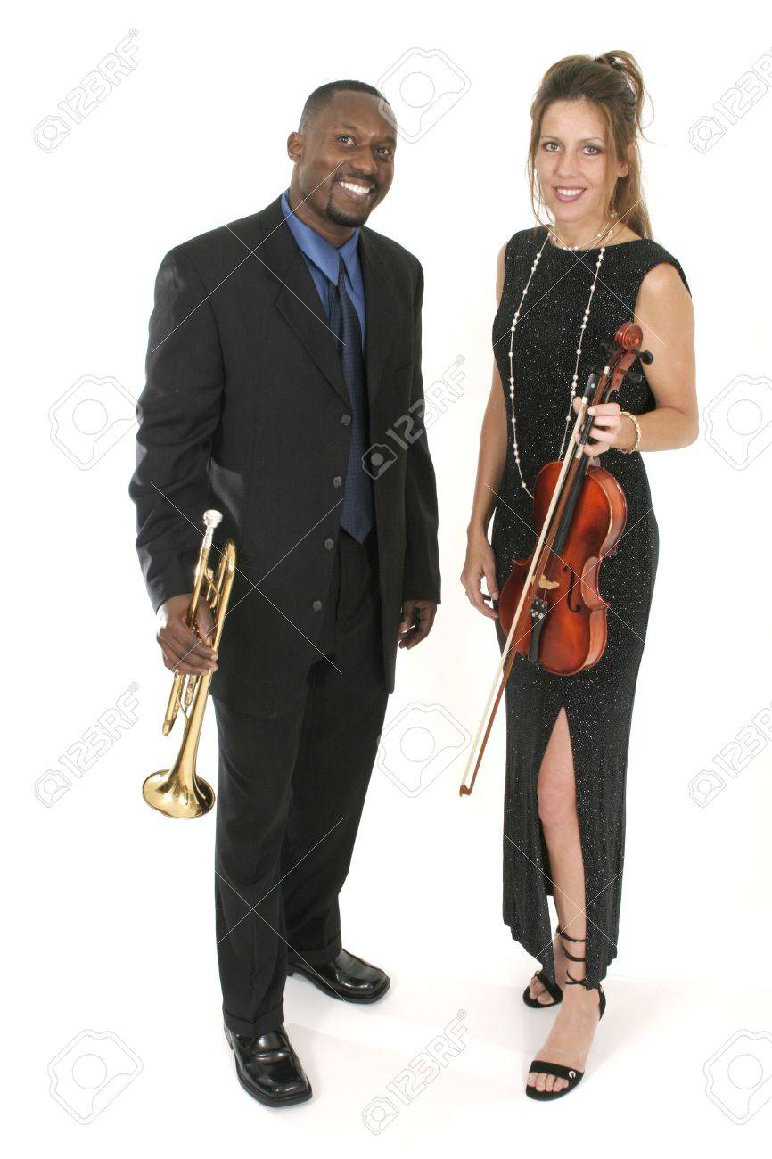 A beautiful female violinist and a handsome male trumpet player standing together holding their instruments.  Shot isolated on white background. Stock Photo - 493147