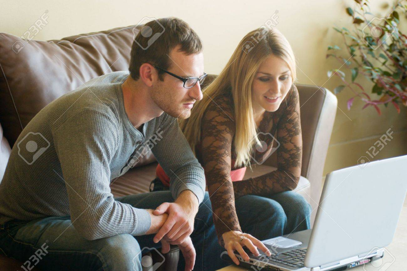 Attractive young man and woman sitting on a couch looking at a laptop computer together.  The focus is on the man closest to the computer.  The woman is slightly out of focus. Stock Photo - 565740