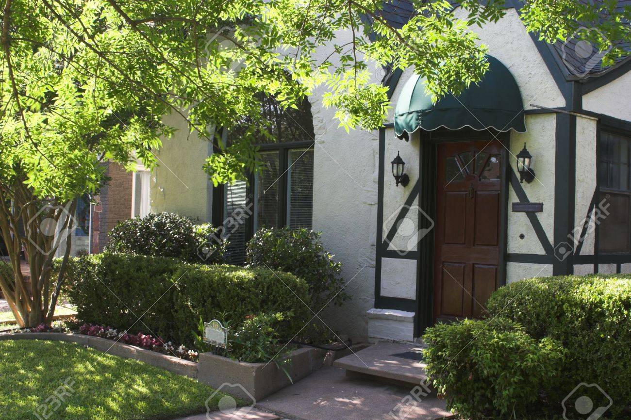 attractive entryway to tudor style house with wood door and green awning; surrounded by foliage and landscaping Stock Photo - 795747