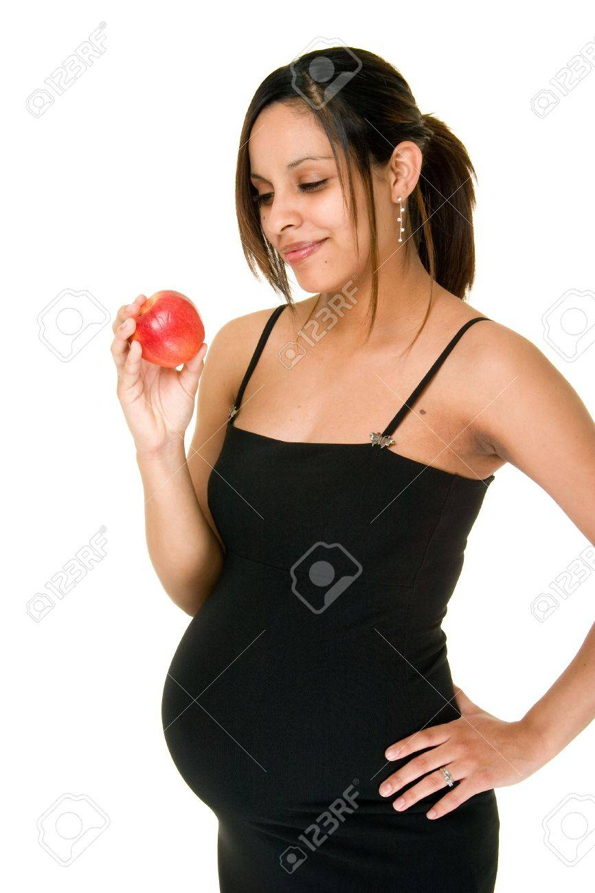 eine schöne junge schwangere frau in einem abendkleid macht eine gesunde  wahl der einen apfel für einen snack.
