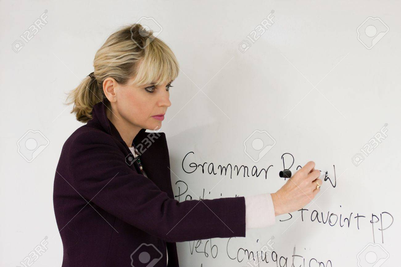 Woman teacher or instructor in a college, university, high school, middle school, elementary classroom writing on a white board with a marker pen. Stock Photo - 6320984
