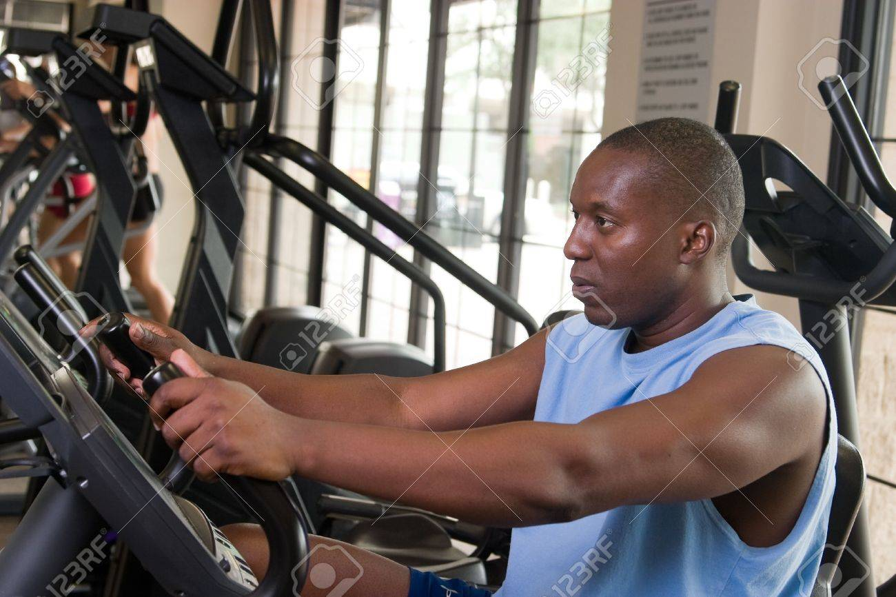 Man working out on a stationary cycle machine in a fitness club. Stock Photo - 6321021