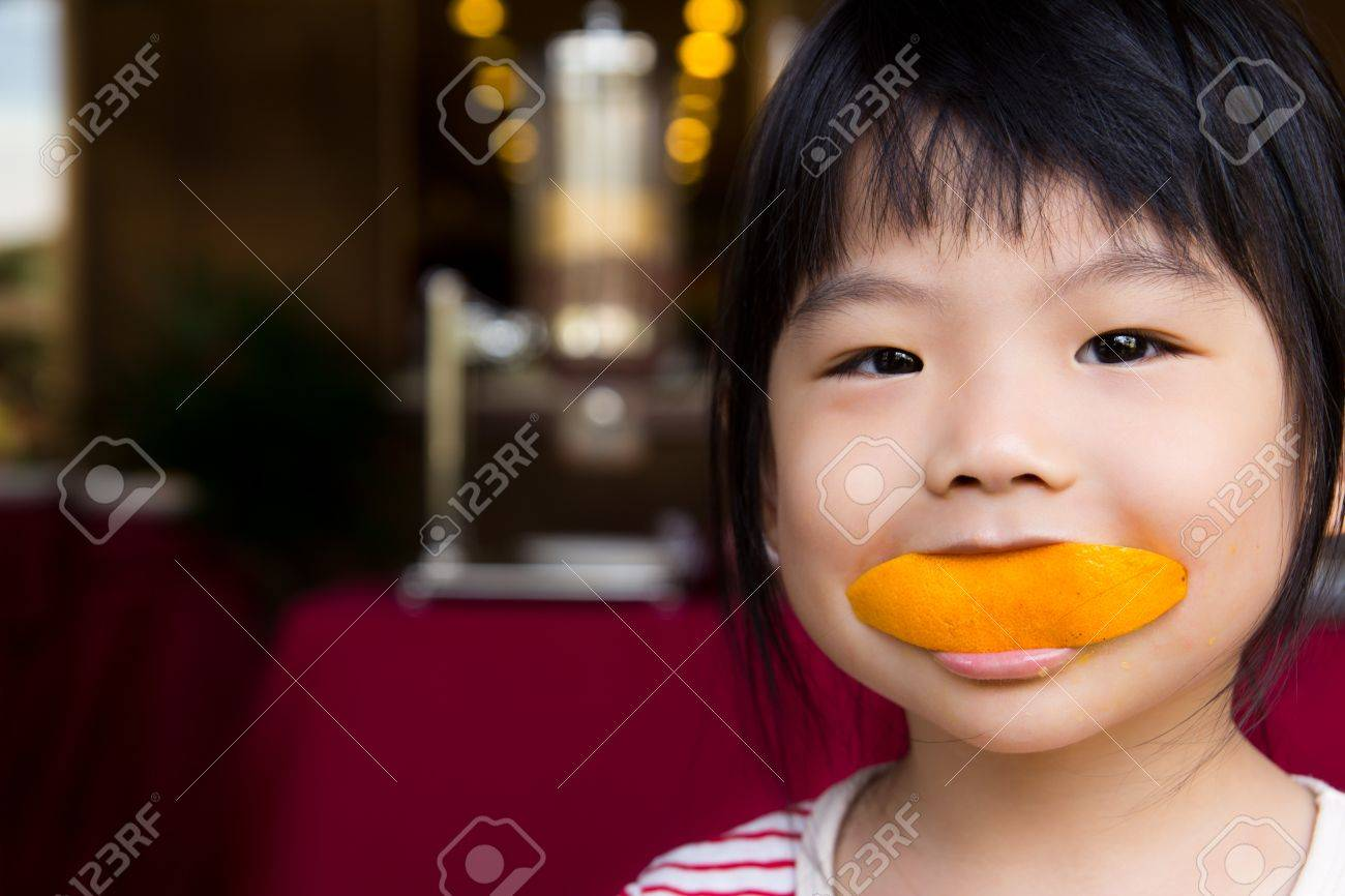 Adorable little girl eating a slice of orange with smiling face Stock Photo - 11158608